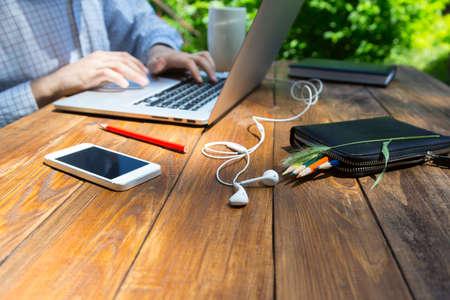 Subido escritorio de madera hecha a mano con los auriculares de teléfonos inteligentes lápices y pieza hierba cuerpo masculino duro trabajo en su correo electrónico en la computadora portátil Foto de archivo - 50296057