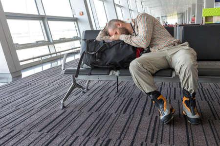 gente durmiendo: Hombre acostando en su equipaje que se espera para el deporte de la salida del tren elegante camisa blanda código de vestimenta relajada casual y pantalones de botas de invierno pesados ??fondo interior