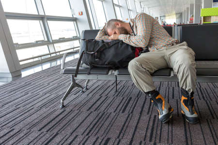 couching: Man couching on his luggage waiting for train departure sport smart casual relaxed dress code soft shirt and pants heavy winter boots interior background