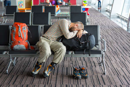 Body of male on foreground sleeping on his luggage lying in chair other people miscellaneous actions on background terminal interior with large windows