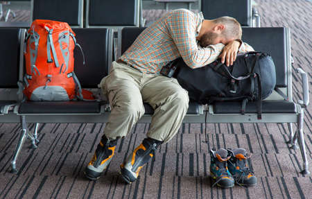 Man sleeping on his luggage lean onto large backpack heavy winter boots and smaller pair aside airport terminal building interior