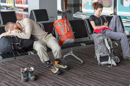 gente durmiendo: Man and woman sitting in chairs line sleeping browsing smart phone internet casual dress code heavy boots backpacks luggage building interior
