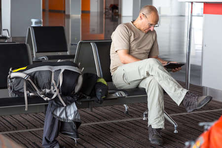 dress code: Mature man using tablet PC sitting inside airport terminal building chair line interior day informal simple dress code large cabin luggage sport backpack