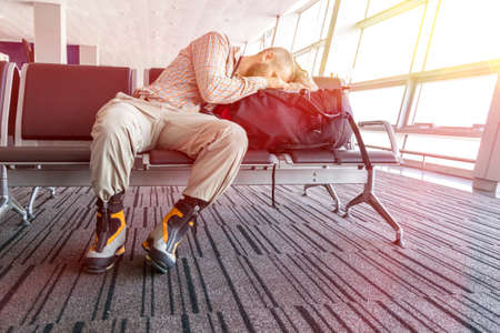 Canceled flight Man sleeping on his travel luggage inside airport terminal with back light bright sun coming throw window