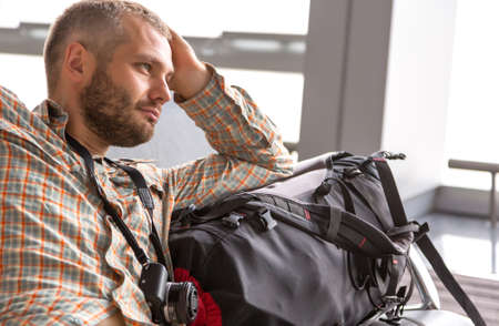 Man sitting in airport lounge terminal casual shirt backpack baggage looking into far calm pensive face Stock Photo