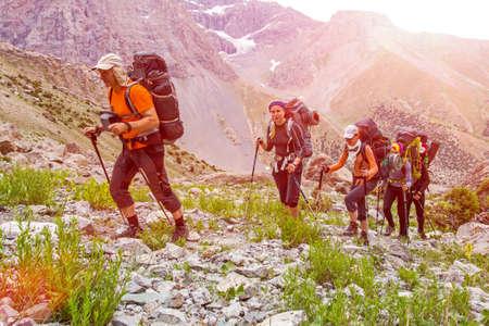 backpack: Excursionistas caminar en el sendero de piedra cubierta de hierba en la India Nepal Himalaya hasta la atracción de alta altitud equipaje pesado y equipo de trekking de montaña picos día soleado de fondo