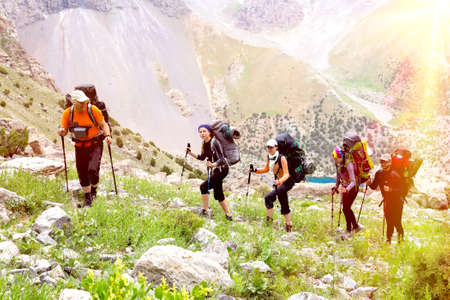 Men and women going up with backpack luggage and hiking gear on bright mountain landscape background with sun rising and high peaks behind 스톡 콘텐츠