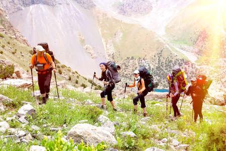 personas unidas: Los hombres y las mujeres que suben con el equipaje mochila y senderismo engranaje en el fondo brillante paisaje de monta�a con el sol y las altas cumbres detr�s