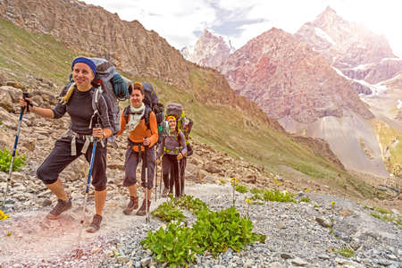 Mountain landscape and people walking with poles backpacks and other gear along dusty Asian trail with green grass and orange rocks around