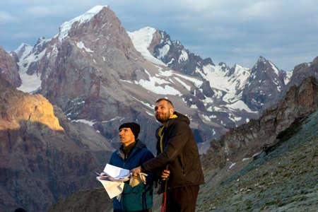 Zwei Menschen alt und junger Mann Bergweg Haltung Stapel von Papieren mit Routenbeschreibung Führer gedruckt Gesichter diskutieren hervorgehoben letzten Sonnenstrahlen warme Sonne