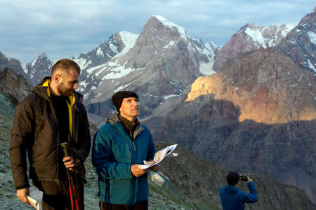 ambiguity: Two people old and young man discuss mountain way keeping stack of papers with route description guidebook printed faces highlighted last sunbeams warm sun