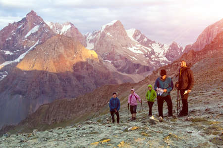 ethnic people: Multinational group of hikers staying on mountain pass with high peaks and rising sun on background