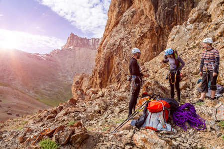 Three people male female placing gear packing backpacks staying on rocky terrain at beginning of Climbing Route on Mountains blue Sky and Sun Rising Background Stockfoto