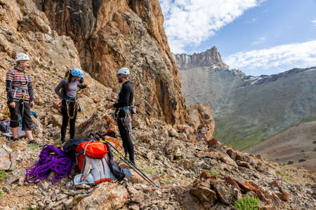 Three people male female talking each other about plan of climb and using gear staying on red rocky terrain high mountain landscape background Stock Photo