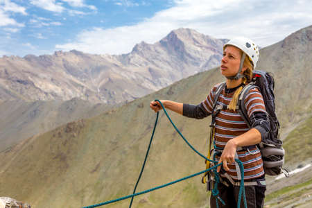 belay: Young cute woman holding alpine rope belay her partner looking up sport gear white protection helmet safety harness many chocks and nuts mountain landscape background