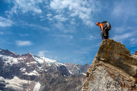 strong base: Rocky razor sharp pointed summit and silhouette of male climber staying on sky and remote high land ridge background daylight sunny day outdoors