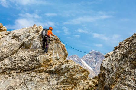 Male mountain climber moving on extreme sharp rock blue sky background climbing gear rope Stock Photo
