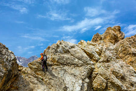 belaying: Body of man moving along mountain cliff with belaying protection rope behind blue sky sunny background