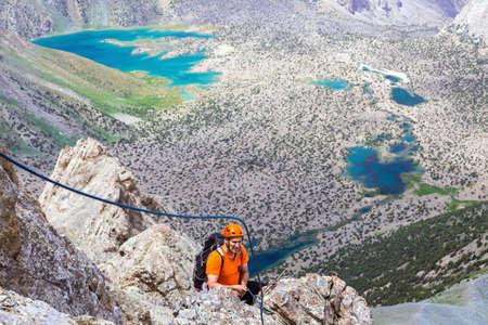 belaying: Elder man orange jacket protection helmet holding belaying rope rocky cliff arranging descent wild vivid color mountain lakes on background Stock Photo