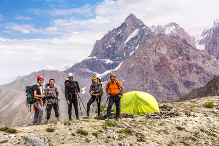 grupo de hombres: Group of five people men and women staying along green camping tent on majestic mountain landscape of deserted Asian area