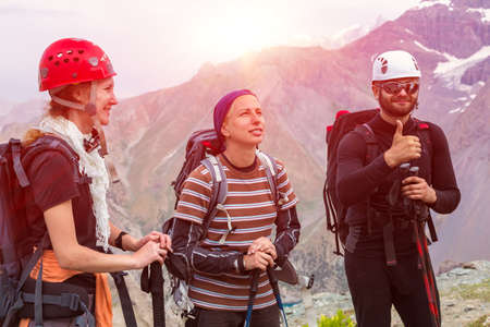 team sport: Three people man and women smiling faces positive expression well gesture high peaks background climbing safety protection gear helmets Stock Photo