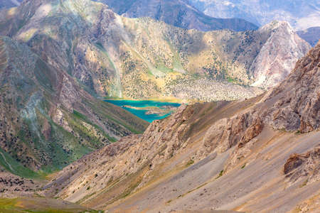 extreme terrain: Landscape of extreme terrain with red tone rocky ridge and green blue water lake sunlight day Stock Photo