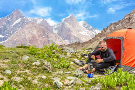 personas comiendo: Hiker sitting in his orange camping tent and having lunch stove and cooking gear mountain landscape on background
