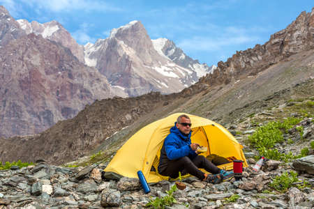 camping tent: Climber sitting in yellow single tent set up rocky terrain camping stove plate bread mug eat cooked lunch high mountains and blue sky background