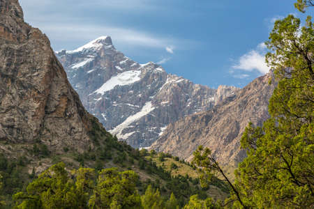 abrupt: Mountain view with sharp peak and vertical rocky wall with glaciers and snow