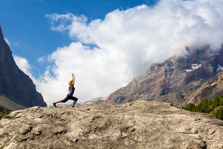 finesse: Attractive Young Woman Doing a Yoga Pose for Balance and Stretching Staying on Top of High Rock in Mountains with Bright Sun Shining on Background