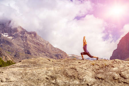 Young woman body on top of stone rock stretching body sunny morning mountain landscape background with arms raised up