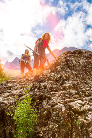 scrambling: People walking on top of stone rock with trekking poles and backpacks silhouettes on clouds and sky background mountain landscape young women
