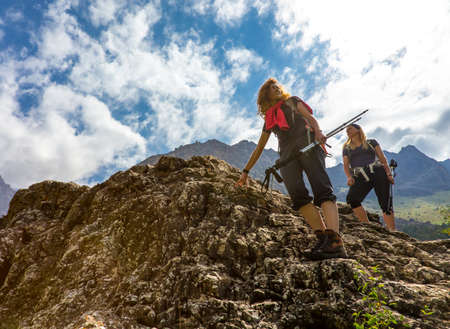 scrambling: Female tourists scrambling steep rocky wall with Mountain Landscape and bright Sun on Background