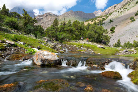 Rapid water stream of river on foreground and group of people hiker walking up hill footpath on background with bright sun shining Stock Photo