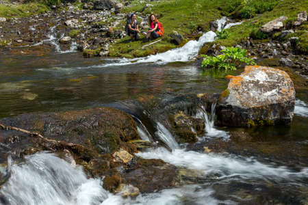 brooks camp: Rapid clean creek vivid colors rocks two young people making stop to relax and drink water
