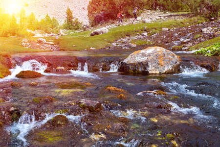 brooks camp: Rapid water stream of river on foreground and group of people hiker walking up hill footpath on background with bright sun shining Stock Photo