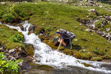brooks camp: Female outdoor enthusiast leaning to rapid mountain creek with rapid flow drinking water washing face green meadow and forest on background