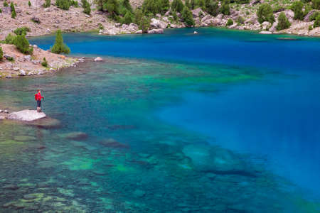 rock bottom: Vivid Green Blue Azure Water Surface of Lake with Transparent Pure Water and Sones Visible on Bottom Body Hiker Staying on Rock Among