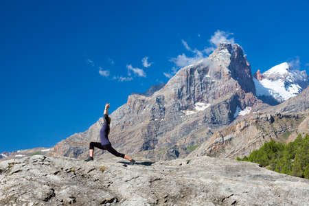 finesse: Cute Girl Doing Yoga Fitness to Stretch Body Staying on High Rock at Mountain Panoramic Landscape Outdoor Sunny Sky Peaks Wilderness Country Smiling Beautiful Face