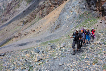 conquer adversity: Hiker Team Scramble Up on Rocky Trail with Severe Colored Steep on Background Stock Photo