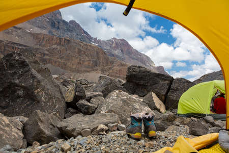 vanishing point: Mountain Landscape from Camping Tent Vanishing Point Steep Rocky Terrain and Hiking Boots Gear