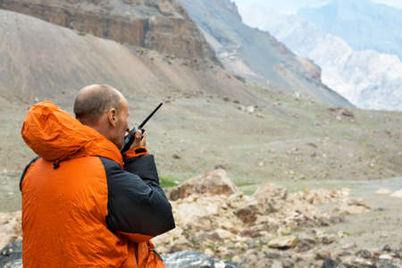 Mountain Rescue Officer Holding Radio Walkie Talkie and Severe Mountain Landscape Background