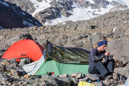 bivouac: Mountain Expedition Camp Green and Red Tents Woman Sitting and Eating Meal Drinking Tea Steep Rocky and Ice Wall on Background Stock Photo