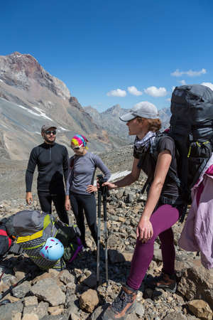 purposefulness: Three people male female placing gear packing backpacks staying on rocky terrain at beginning of Climbing Route on Mountains blue Sky and Talking Gesturing