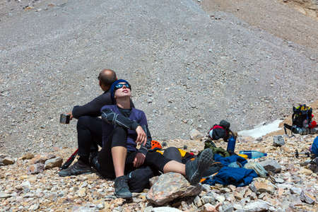 Female and Male Travelers lean on each other Totally Tired After Difficult Ascent Alpine Gear Dropped Around Backpacks Helmets Rocky Moraine on Background Stockfoto