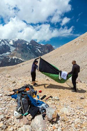 多くのギアを落として周りと背景にロッキー山モレーンのテントのキャンプを設定する高山の登山者のグループ 写真素材