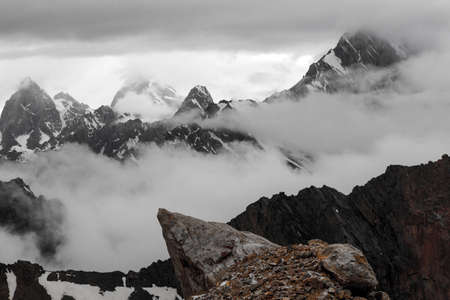 ridges: Landscape with Several Layers of Rocky Snowy Ridges mainly in Black and White Except Orange Rock on Foreground Overcast Clouds Sky