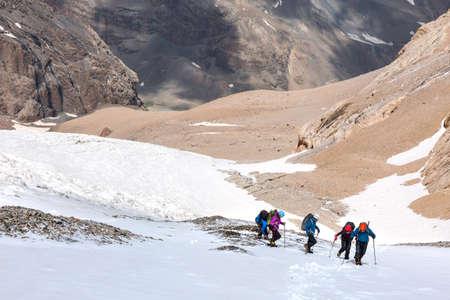 snow climbing: Trekking Himalaya Hikers Walking Up Glacier in Nepal India Himalaya Way up to high altitude Snow Climbing trekking gear mountain sunny day Rock Moraine background