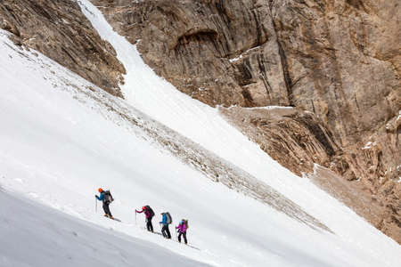 snowfield: Members of Alpine Expedition Hardly Walking Up on Steep Snowfield Using Ice Climbing and Hiking Gear