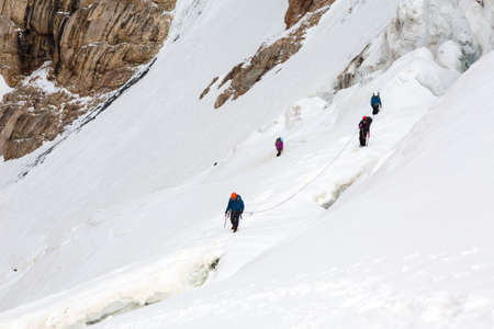 belay: Members of Alpine Expedition Walking Up on Steep Snowfield Using Ice Climbing and Hiking Gear Dangerous Crevasses Rope Belay Led by Mature Guide